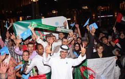 População comemora depois que Dubai ganhou o direito de sediar a Exposição Mundial de 2020, em frente ao Burj Khalifa, em Dubai, nesta quarta-feira. 27/11/2013 REUTERS/Mohammed Omar