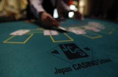 A logo of Japan casino school is seen as a dealer puts cards on a mock black jack casino table during a photo opportunity at an international tourism promotion symposium in Tokyo September 28, 2013. REUTERS/Yuya Shino
