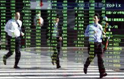 Pedestrians are reflected on a stock quotation board at a brokerage in Tokyo November 26, 2013. REUTERS/Yuya Shino