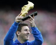Barcelona's soccer player Lionel Messi poses with the Golden Boot trophy before their Spanish first division league match against Granada at Camp Nou stadium in Barcelona November 23, 2013. REUTERS/Albert Gea