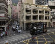 A man rides a bicycle next to a tram passing by a Chinese pawn shop that has been restored and partially converted into a restaurant at Hong Kong's Wanchai district in this February 1, 2013 file picture. REUTERS/Tyrone Siu/Files