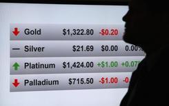 Человек стоит у экрана с котировками драгоценных металлов во время конференции Denver Gold Forum в Денвере 24 сентября 2013 года. Рынок золота завершает ноябрь сильнейшим спадом с июня, поскольку рост американской экономики заставляет инвесторов переводить средства на быстрорастущие фондовые рынки. REUTERS/Rick Wilking