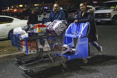 Shoppers walk with a cart full of purchases from Walmart in Westbury, New York, November 29, 2013. REUTERS/Shannon Stapleton