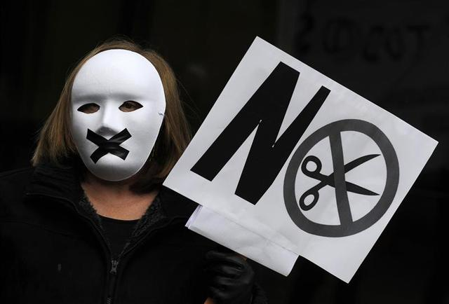 A protestor wears a mask with black tape over the mouth during a demonstration against government austerity measures and the passing of a new law by the cabinet which toughens penalties on protesters, in Oviedo, northern Spain, November 29, 2013. REUTERS/Eloy Alonso