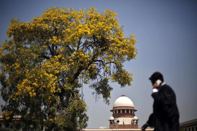 A lawyer speaks on his mobile phone as he walks past India's Supreme Court in New Delhi April 1, 2013. REUTERS/Adnan Abidi/Files