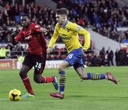 Cardiff City's Kevin Theophile-Catherine (L) challenges Arsenal's Aaron Ramsey during their English Premier League soccer match at Cardiff City Stadium in Cardiff, Wales, November 30, 2013. REUTERS/Rebecca Naden