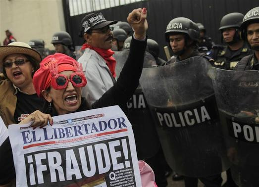 A supporter of Xiomara Castro, presidential candidate of the Liberty and Refoundation party (LIBRE), holds up a poster with the word 'Fraud' written on it, as she demonstrates next to riot police officers standing guard during a protest against the results of the presidential election in Tegucigalpa December 1, 2013. REUTERS-Jorge Cabrera