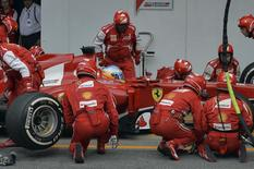 Ferrari Formula One driver Fernando Alonso of Spain is attended to by his crew during a pit stop during the Brazilian F1 Grand Prix at the Interlagos circuit in Sao Paulo November 24, 2013. REUTERS/Nelson Almeida
