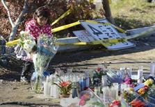 """Menina coloca flores no local do acidente de carro onde o ator Paul Walker foi morto na região de Santa Clarita, em Los Angeles. A alta velocidade contribuiu para o acidente que matou no sábado o ator Paul Walker, astro da série """"Velozes e Furiosos"""", segundo autoridades da região de Los Angeles. 01/12/2013. REUTERS/Phil McCarten"""