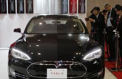 People take pictures of a Tesla Model S car, displayed at the 43rd Tokyo Motor Show November 20, 2013. REUTERS/Yuya Shino