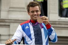 Diver Tom Daley holds his bronze medal during a parade through London September 10, 2012. REUTERS/Neil Hall