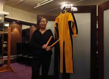 """Anna Lee, vice chairman of Chinese auction house Spink, poses with nunchaku and a jumpsuit, both used by the late kungfu superstar Bruce Lee in his last movie """"Game of Death"""", as part of the Bruce Lee 40th anniversary collection, at a news conference in Hong Kong December 2, 2013. REUTERS/Bobby Yip"""