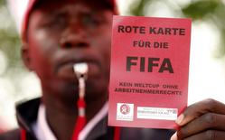 Член швейцарского профсоюза UNIA держит красную карточку во время акции протеста у штаб-квартиры ФИФА в Цюрихе 3 октября 2013 года. Всего за четыре дня до проведения жеребьевки чемпионата мира по футболу 2014 года прокурор Сан-Паулу начал расследование на предмет возможного проявления расизма со стороны ФИФА. REUTERS/Arnd Wiegmann