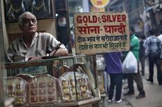 Продавец ювелирного магазина в Дели 7 октября 2013 года. Цены на золото близки к пятимесячному минимуму, так как высокие экономические показатели США вызвали опасения скорого окончания стимулирующей программы ФРС. REUTERS/Mansi Thapliyal