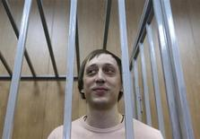 Former Bolshoi Theatre dancer Pavel Dmitrichenko stands inside the defendant's cage during a court hearing in Moscow December 3, 2013. REUTERS/Maxim Shemetov