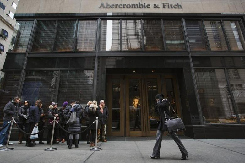 A pedestrian walks past shoppers lined up to wait for the opening of an Abercrombie & Fitch store in New York, November 26, 2013. REUTERS/Lucas Jackson