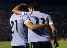 Atacante do Uruguai Cavani abraça companheiro de equipe Stuanis após marcar gol em partida contra a Argentina, em Montevidéu. 15/10/2013 REUTERS/Andres Stapff