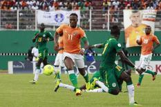 O atacante Didier Drogba, de Costa do Marfim, disputa lance com jogadores do Senegal, em outubro. REUTERS/Thierry Gouegnon