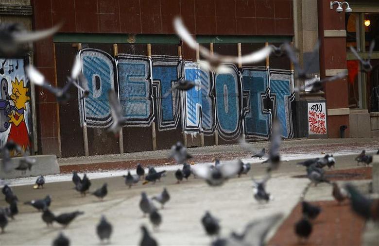 Pigeons are seen near graffiti in Detroit, Michigan, December 3, 2013. REUTERS/Joshua Lott