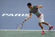 Australia's Bernard Tomic hits a return to Feliciano Lopez of Spain during the opening round match of the Paris Masters men's singles tennis tournament at the Palais Omnisports of Bercy in Paris October 28, 2013. REUTERS/Charles Platiau
