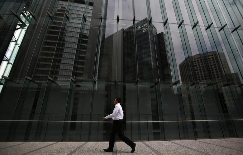 A man walks on a pathway next to a building in Tokyo's business district September 30, 2013. REUTERS/Yuya Shino