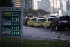 Os preços de gasolina, álcool e diesel vistos na placa de um posto de combustível, ao lado do tráfego na praia de Copacabana no Rio de Janeiro. A aplicação de reajustes aos preços de combustíveis não será automática como resultado da fórmula de precificação aprovada no fim da semana passada pelo Conselho de Administração da Petrobras, informou a estatal nesta quarta-feira. 29/11/2013 REUTERS/Ricardo Moraes