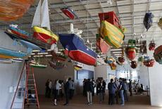 """Media members stand near a work titled """"For Those in Peril on the Sea"""" by artist Hew Locke during a tour of the Perez Art Museum Miami (PAMM) in Miami, Florida December 3, 2013. REUTERS/Joe Skipper"""