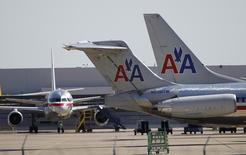 American Airlines airliners sit near a hanger at Dallas/Fort Worth International Airport, Texas April 4, 2012. REUTERS/Tim Sharp