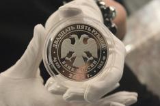 Коллекционная монета номиналом 25 рублей на презентации в Москве 25 апреля 2012 года. Рубль умеренно дорожает утром четверга за счет корпоративных денежных потоков. REUTERS/Yana Soboleva