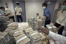 Employees count and pack money inside a bank in Yangon November 14, 2013. REUTERS/Minzayar