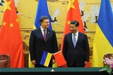 Президент Украины Виктор Янукович и председатель КНР Си Цзиньпин на церемонии подписания документов в Пекине 5 декабря 2013 года. Президент притормозившей интеграцию с Западом Украины сообщил в четверг из Китая, что заручился здесь обещаниями инвестиций на $8 миллиардов, способных поддержать на плаву замедляющуюся экономику задолжавшей страны, охваченной массовыми уличными выступлениями. REUTERS/Wang Zhao/Pool
