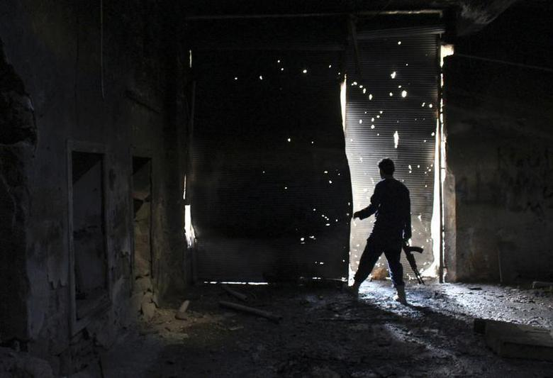 A Free Syrian Army fighter carries his weapon as he peeks out from a damaged shop in the old city of Aleppo November 29, 2013. REUTERS/Mahmoud Hebbo
