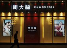 A man walks past a Chow Tai Fook shop in Yichang, Hubei province, September 3, 2013. REUTERS/China Daily