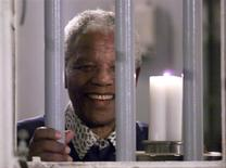 Former South African President Nelson Mandela holds a symbolic millennium candle through the bars of the prison cell in which he was incarcerated on Robben Island, in this December 31, 1999 file photo. REUTERS/Mike Hutchings/Files