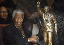 Former South African president Nelson Mandela (front L) speaks with an aide behind a statue of him that was unveiled at Groot Drakenstein prison in Paarl near Cape Town, in this file picture taken August 21, 2008. REUTERS/Howard Burditt/Files