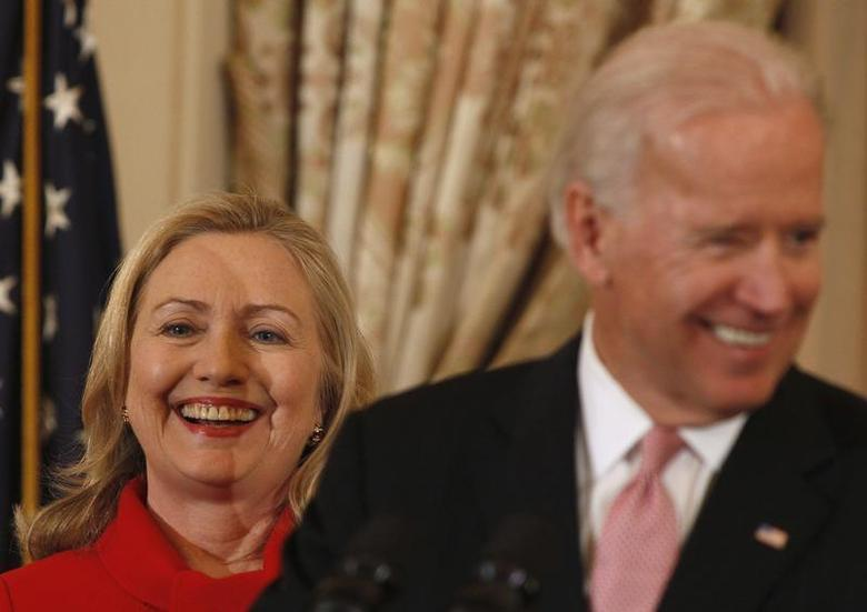 U.S. Secretary of State Hillary Clinton (L) listens to U.S. Vice President Joseph Biden during a luncheon for China's Vice President Xi Jinping at the State Department in Washington February 14, 2012. REUTERS/Larry Downing