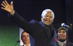 Nelson Mandela waves from the stage with British Prime Minister Tony Blair (L) and South African High Commissioner Cheryl Carolus at Trafalgar Square during the South African democracy concert, in this April 29, 2001 file photo. REUTERS/Files