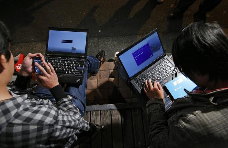 Men install Microsoft Corp's Windows 8 operating system on their laptops, as Windows 8 goes on sale after midnight, along a street at the Akihabara district in Tokyo October 26, 2012. REUTERS/Toru Hanai