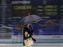 A woman walks past a stock quotation board outside a brokerage in Tokyo September 2, 2013. REUTERS/Toru Hanai