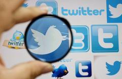 Человек смотрит через увеличительное стекло на логотип Twitter на экране компьютера в Скопье 20 сентября 2013 года. Twitter Inc в сотрудничестве с небольшой компанией из Сингапура работает над тем, чтобы сделать свой сервис отправки коротких сообщений доступным пользователям из развивающихся стран, имеющим простые телефоны, которые не могут подключаться к интернету. REUTERS/Ognen Teofilovski