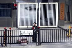 Полицейский охраняет въезд в посольство Южной Кореи в Пекине 6 декабря 2013 года. Северная Корея столкнулась, возможно, с самим серьезным за долгие годы дезертирством после того, как помощник лишенного своих постов во власти дяди лидера КНДР Ким Чен Ына сбежал из изолированной страны, сообщили в пятницу южнокорейские СМИ. REUTERS/Jason Lee