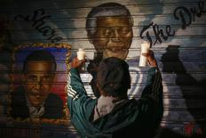 A man holds candles in front of a mural of former South African President Nelson Mandela (C) and U.S. President Barack Obama in New York, December 5, 2013. REUTERS/Shannon Stapleton