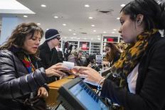 Una cliente realiza una compra en una tienda de la cadena Express en Nueva York, nov 29 2013. La confianza del consumidor estadounidense subió con fuerza en los primeros días de diciembre debido a una mejoría en el panorama sobre la economía y el empleo en Estados Unidos, mostró el viernes un informe. REUTERS/Lucas Jackson
