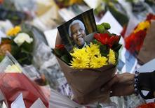 Flowers and tributes are left for South Africa's former president Nelson Mandela at South Africa's High Commission in London December 6, 2013. REUTERS/Luke MacGregor
