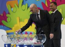 Former French soccer player Zinedine Zidane draws a ball from a pot as former Brazilian soccer player Cafu looks on, during the draw for the 2014 World Cup at the Costa do Sauipe resort in Sao Joao da Mata, Bahia state, December 6, 2013. REUTERS/Ricardo Moraes