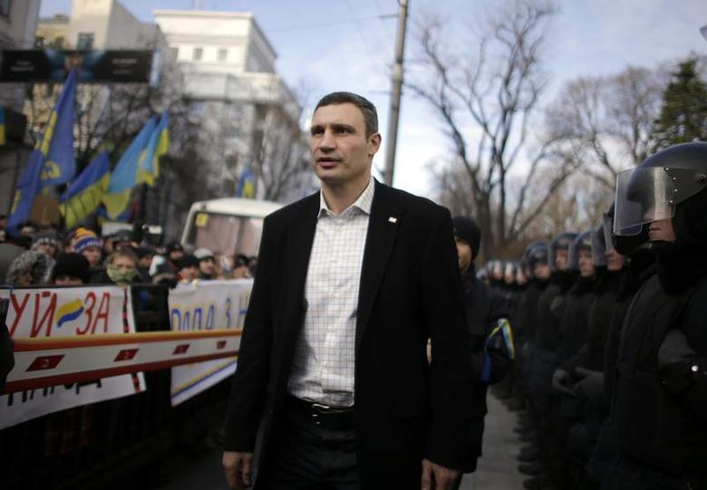 Vitali Klitschko, heavyweight boxing champion and UDAR (Ukrainian Democratic Alliance for Reform) party leader, walks past supporters and police outside the parliament in Kiev December 3, 2013. REUTERS/Stoyan Nenov