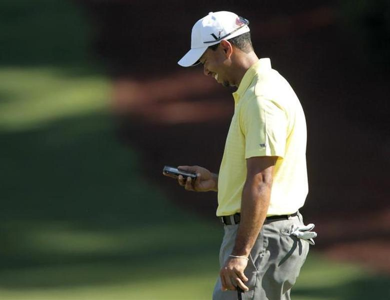 Tiger Woods of the U.S. looks at his iPhone after using it to take a picture of playing partner Mark O'Meara on the 10th green, during a practice round for the 2010 Masters golf tournament at the Augusta National Golf Club in Augusta, Georgia, April 6, 2010. REUTERS/Hans Deryk