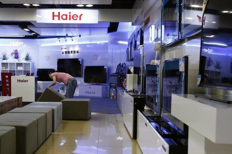 An employee arranges stools at a section displaying Haier television sets inside a Suning store in Shanghai August 26, 2013. REUTERS/Aly Song