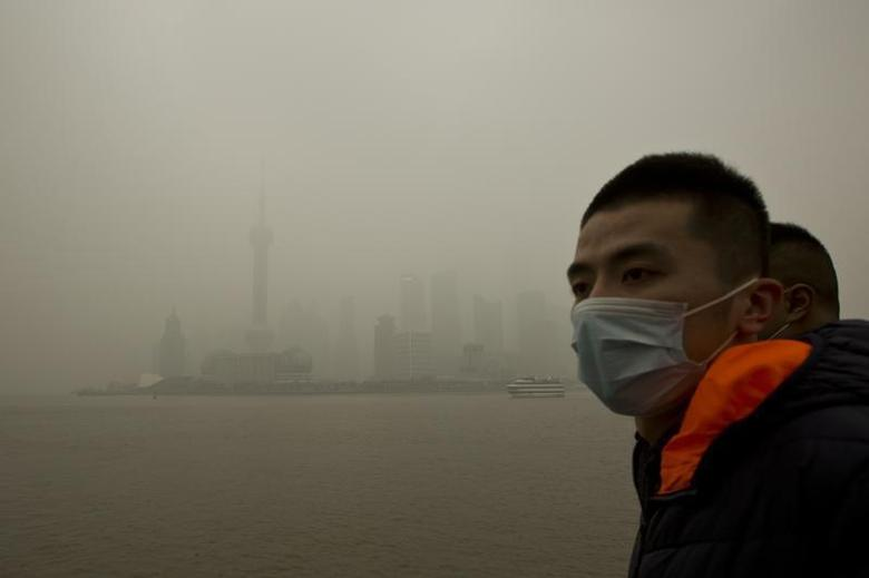 A man wears a face mask while walking on the Bund in front of the financial district of Pudong during a hazy day in downtown Shanghai December 9, 2013. REUTERS/Aly Song