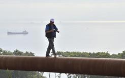 Мужчина идет по трубе газопровода на острове Русский близ Владивостока 23 августа 2011 года. Российский концерн Газпром почти на 20 процентов увеличивает суммарные расходы на строительство экспортной трансчерноморской магистрали Южный поток, проектируемой в обход Украины, которая задолжала экспортеру более $2 миллиардов за поставленный в 2013 году газ. REUTERS/Yuri Maltsev
